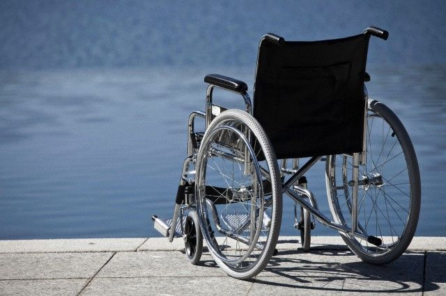 Wheelchair parked by water --- Image by © Walter Zerla/cultura/Corbis