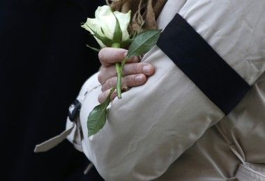A woman holds a white rose as she observes a minute's silence in memory of the victims of the Paris shootings, at St George's Hall in Liverpool, Britain November 16, 2015. REUTERS/Phil Noble