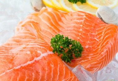 Fresh fillets of salmon on ice with clams and lemon