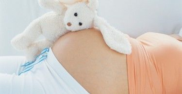 Stuffed rabbit on top of pregnant woman's belly --- Image by © Heide Benser/Corbis
