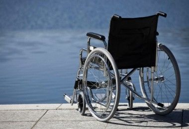Wheelchair parked by water --- Image by © Walter Zerla/cultura/Corbis